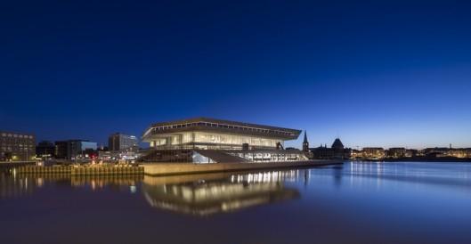 Het gebouw van de bibliotheek Aarhus, gelegen aan het water, bij avond gefotografeerd.