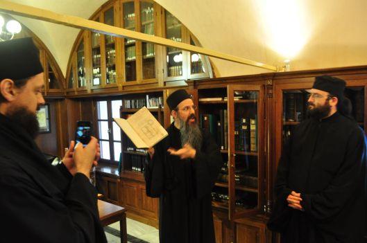 Monnik toont en kostbaar boek in een kloosterbiblotheek op Athos