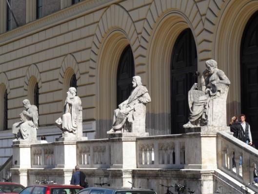 4 standbeelden voor de hoofdingang van de Bayersche Staatsbibliothek. V.l.n.r.: geschiedschrijver Thucydides, dichter Homeus, wijsgeer Aeistoteles en arts Hippocrates.