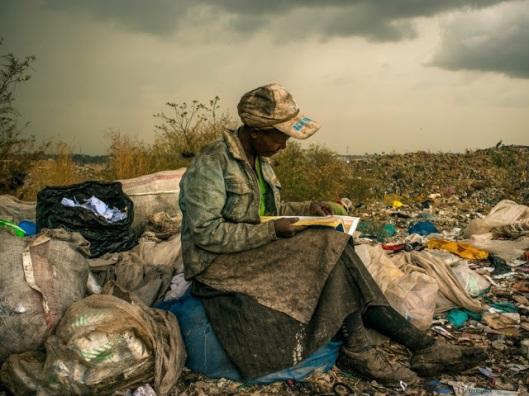 Keniaanse vrouw met een gevonden boek op de vuilnisbelt van Nairobi (foto Micah Albert)