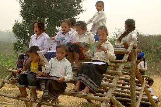 Kinderen van een lagere school in Laos lezen met de onderwijzeres hun eerste boek (Wikipedia Commons)