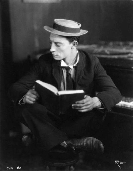 Buster Keaton zittend voor een boek kijkt om (Marie Aimée Canteras)