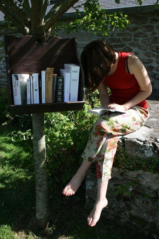 Lezend bij een vrije openbare minibibiotheek (Improbables Libraries, Improbables Bibliothèques)