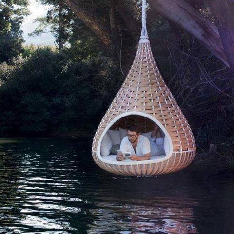 Al lezende hangende aan een brug boven het water (Improbables Libraries, Improbables Bibliothèques)