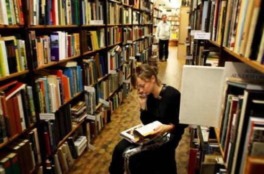 Telefonerend lezen tussen de boekenkasten van De Slegte in Amsterdam (Roger Cremers)