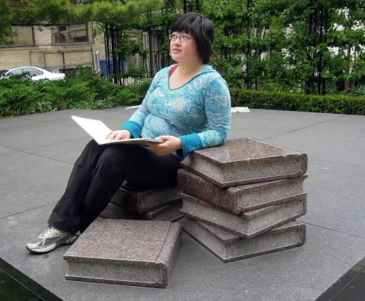 Lisa Hsia met een open boek op boeken van steen -monument in Toronto, Canada