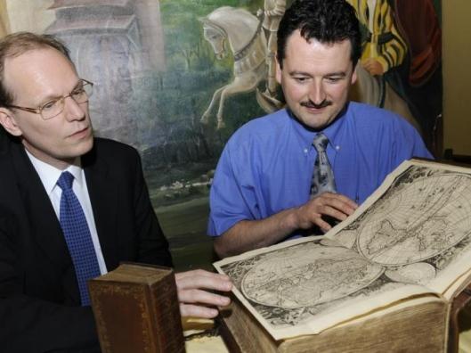 Boekentaxateur Arie Molendijk (links) en bijbelvertaler Marc Claeys bekijken een antieke bijbel