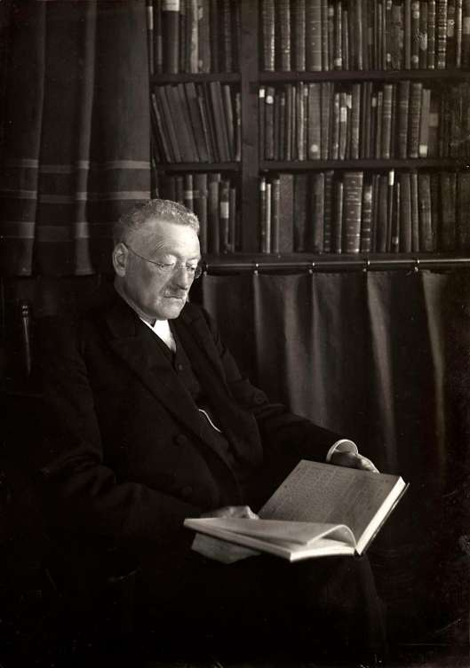 Rabbijn Philip Elte uit Amsterdam een boek lezend in zijn bibliotheek