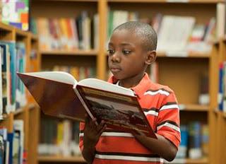 Lezende jongen in Amerikaanse jeugdbibliotheek (Philip S.)