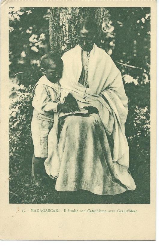 Grootmoeder leest met kleinkind uit Madagascar de catechismus