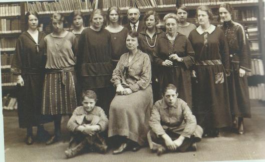 Groepsportret van het personeel openbare bibliotheek Dordecht in 1924. Enige man was bode en binder J.van Vliet. Vooraan directrice me. Nel Snouck Hurgronje en twee jongens die in de binderij meehielpen.