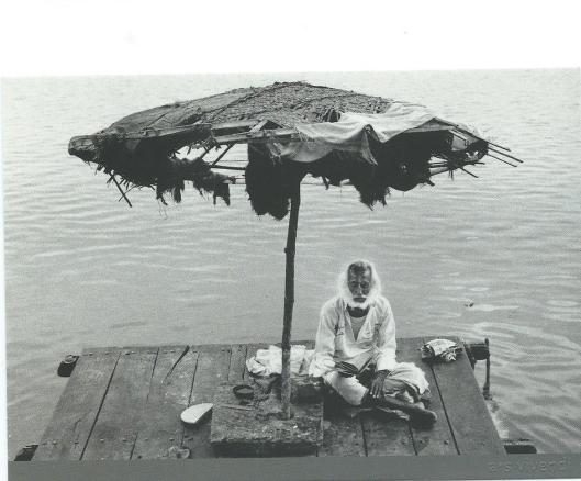 Een sadhoe lezend op een steiger in de Ganges in India (foto Rudolf Dietrich)