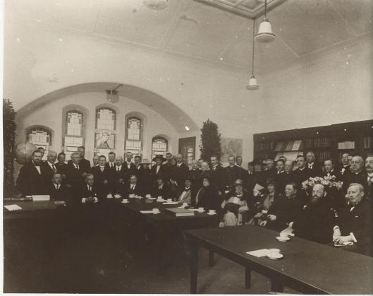 Opening van de leeszaal in de Willem-II straat 23 te Tilburg op 30 maart 1922. De genodigden, bestaande uit pastoors, burgemeester en wethouders en bestuurders van de bibliotheek poseren in de meeszaal. In het glas-en-loodraam een portret van dr.J.Weijers (1822-1917), mede-oprichter en eerste voorzitter van de r.k. openbare leeszaal in 1913.