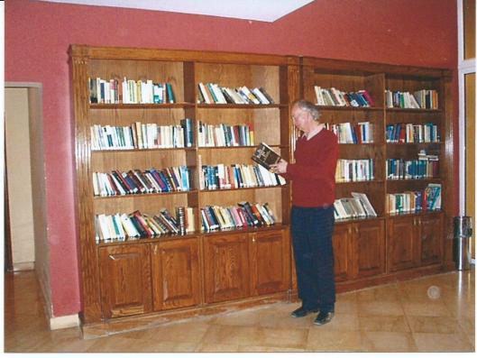 Hans Krol in een hotelbibliotheek bij boekenkast met Duitstalige boeken bij de Dode Zee, Jordanië 2008