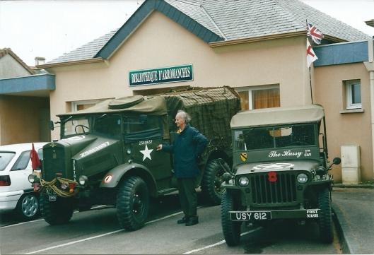 De bibliotheek in het plaatjes Arromaches, Normandië, met tijdelijk militaire voertuigen op de parkeerplaats