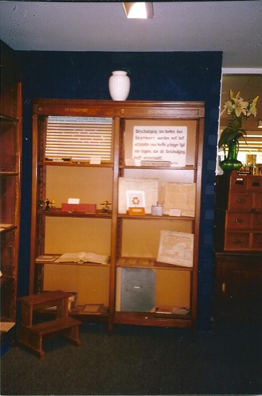Kast met biblio-curiosa, links een bibliotheekbankje en rechts deel van houten catalogusbakken