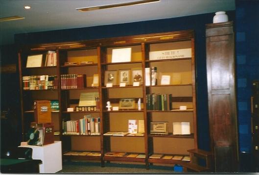 Boekenkast met portretten en curiosa, zoals rechtsboven een bordje STILTE