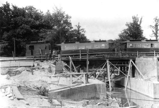 Aanleg van brug over de Van Merlenvaart met passerende stoomtram