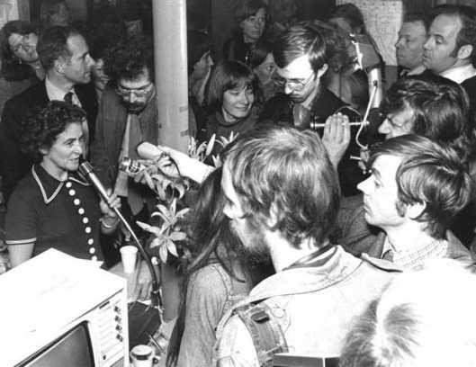 Voorzitter van het stichtingsbestuur mr. Anneke Goudsmit staat te pers te woord en laat weten dat een geplande politie-inval om apparatuur in beslag te nemen voor onbepaalde tijd is uitgesteld (20 mei 1976).