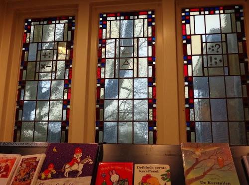 Reken- en leestekens, een passer en een driehoek in glas-en-lood ramen uit 1930 van voormalige Dreefschool, sinds 1986 huisvesting van de openbare bibliotheek (foto Lidia Schoonderend)