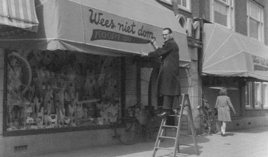 Buitenreclame op markies: 'Wees niet dom, koopt bij Blom' [was een lingeriezaak op de hoek van Legmeerplein met de Weissenbuchstraat in Amsterdam].
