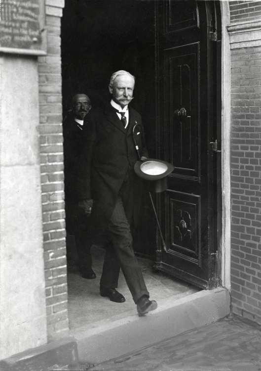 Jhr.mr.J.W.G.Boreel van Hogelanden verlaat in 1912 als afgetreden burgemeester voor de laatste keer het stadhuis van Haarlem. Achter hem wethouder H.D.Kruseman