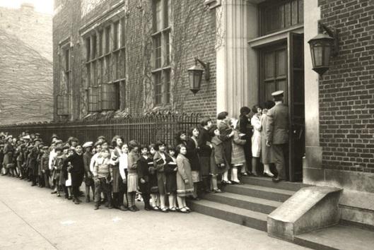 In 2014 bestaat de Brooklyn Public Library 100 jaar. Op deze foto zien we de Stone Avenue Library die oorspronkelijk als eerste kinderbibliotheek is ingericht. Afbeelding uit begin vorige eeuw met een groep kinderen die een boek terugbrengt om een nieuw boek te kunnen lenen.