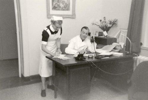 Chirurg dr. van Haag en zuster Postma in dokterskamer, circa 1950