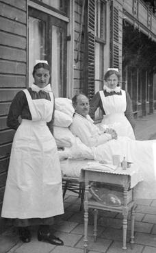 Verpleging in de openlucht: patiënt tussen 2 diaconessen-verpleegsters