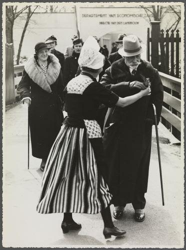 Wilhelm wordt verwelkomd op de Flora 1935 door een bloemenmeisje in Volendamse kledij die hem een corsage opspeldt