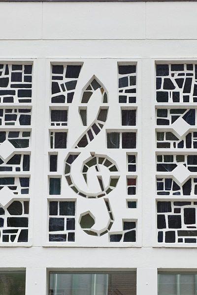 G-muzieksleutel, deel van voorgevel glas-in-beton. Ontworpen door D.Plat voor Bovema, Overboslaan 6, 1959 (foto Rijksdienst voor het Cultureel Erfgoed).