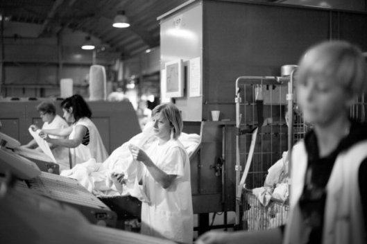 Jongedames aan het werk bij de vouwmachine van wasserij Van Houten/NEWASCO, de laatste wasserij in Heemstede (foto 2011)