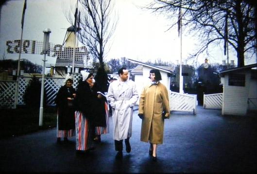 'Women selling programs at Flora 1953 in Hempstead, Netherlands' Een jong stel heeft zojuist de hoofingang nabij de Molenburg gepasseerd en wordt door een jdame in klederdracht aangesproken om een programma te kopen (Door Ruud van der Moolen uit de USA ontvangen dia)