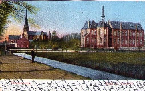 Ansichtkaart van de Kerklaan met zandvaart, het St. Antoniusgesticht en de St. Bavokerk, pastorie en huis.