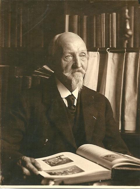 Portret van kunstschilder A.L.Koster, thuis bladerend in een boek