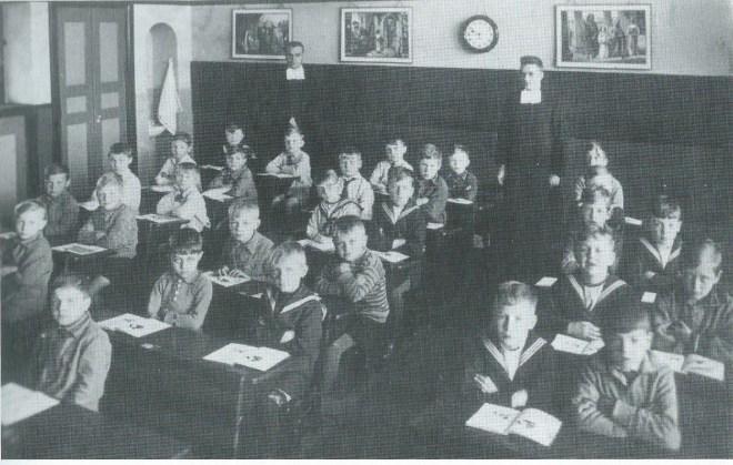 De eerste klas van de Jacobaschool in 1931 Rechts in de klas op de voorste tij: de eerste jongen onbekend, daarnaast Gerrie Dobbe en daarachter Frits Ludwig.
