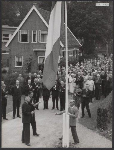 Staatssecretaris van Sociale Zaken B.Roolvink opent de nieuwe sociale werkplaats op instelling Meer en Bosch door de vlag te hijsen, 1 september 1951.