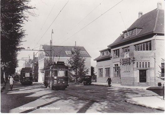 Twee trams kruisen elkaar bij het postkantoor in de Raadhuisstraat. Links de tram richting Heemstede en rechts de tram naar Schoten (Soendaplein)