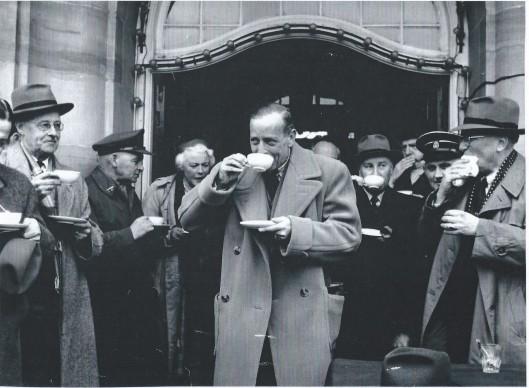 Erwtensoep eten voor Puttershoek in Heemstede na de watersnood van 1953. In het midden burgemeester ridder Van Rappard, links wethouder Van Lent