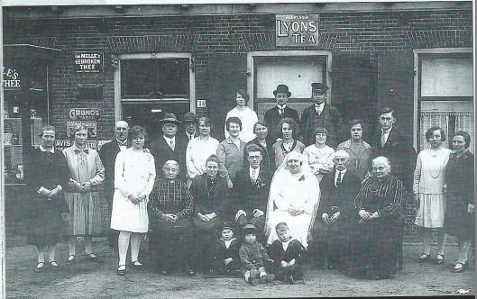 Foto van kruidenierswinkel Hulsebosch, Binnenweg 35 Bennebroek. Op de foto vervaardigd bij een (tweede) huwelijk staan o.a. Rie Hulsbosch (links met strikje), naast de bruid grootvader Hulsbosch , daarnaast de zuster van de bruid en achteraan met pet Karel Hulsbosch.