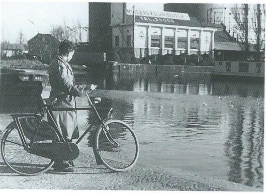 De in 1897 gestichte kolenhandel van Teeuwen aan het haventje. Deze zogenaamde zwaaihaven, via het Heemsteeds kanaal verbonden met het Spaarne is in de jaren twintig van de vorige eeuw gegraven. Achter de kolenhandel staat een gashouder van het gemeentelijk gasbedrijf. Links op de achtergrond staat het huis aan de Nijverheidsweg dat vroeger als ambtswoning fungeerde van de directeur van het gemeentelijk gas-, water- en electriciteitsbedrijf