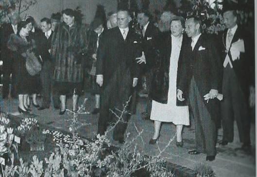De heer Tom Hoog van de firma Van Tubergen leidt koningin Juliana rond op de Flora 1953, stilstaand voor de inzending van de firma C.G.van Tubergen.