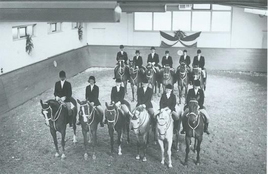 Op Herenweg 78a stond het bedrijfspand van Piet Nelis. Later werd het in gebruik genomen door poetsdoekenfabriek Wallage. Achter het pand lag een manege. Op de foto staan alle paarden met hun ruiters opgesteld. De manege is afgebroken.