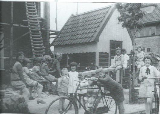 In de jaren dertig van de vorige eeuw is de Raadpensionarissenwijk tot stand gekomen, evenals de Bloemenwijk, voor forensen gunstig gesitueerd nabij de staionshalte Heemstede-Aerdenhout. De meeste huizen in de Van de Spiegellaan zijn van Bouwburau J.E.Baalbergen en A.Volkers. Deze foto is op een zomerse dag gemaakt in een kennelijk kinderrijke buurt. Tussen twee huizen, waarvan het linker (nrs.27/27a) in aanbouw is, staat een bouwkeet. Van een hoop bouwstenen en een plank heeft de jeugd een provisorische wip gemaakt.