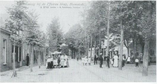 Foto uit begin 1900 toen de Raadhuisstraat nog Binnenweg heette. Het Pleintje rechts was een verzamelpunt van bewoners. Hier was al in 1839 een tapperij gevestigd, later 'de Halte' geheten en in de volksmond café van Toledo. Welgestelden droegen op zondag een driedelig kostuum en hoed, arbeiders een pet. Drukte bij de ijscokar. De heer Küpers, eigenaar van een koperslagerij (later drukkerij Schellekens/Van Assema) kijkt toe voor zijn pand.