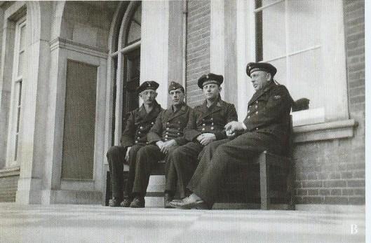 Vier matrozen van de Duitse 'Kriegsmarine' rusten uit op een bank op het bordes van Hageveld