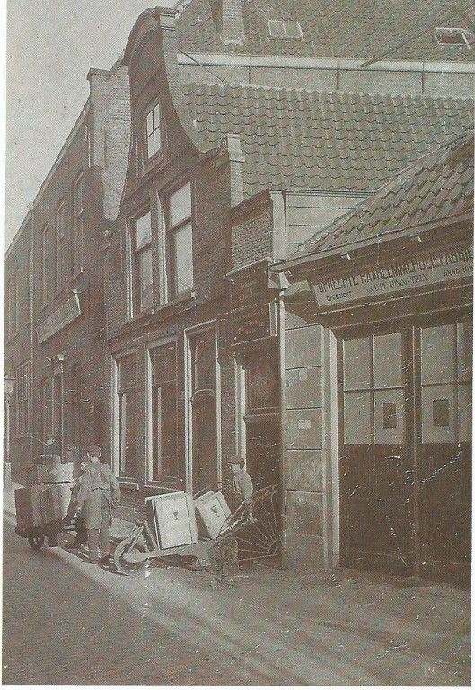 Foto uit omstreeks 1900 van de Haarlemmerolie-fabriek in de Antoniestraat 13-15. Jonge jongens voeren op kruiwagens kisten met het wondermiddel af.