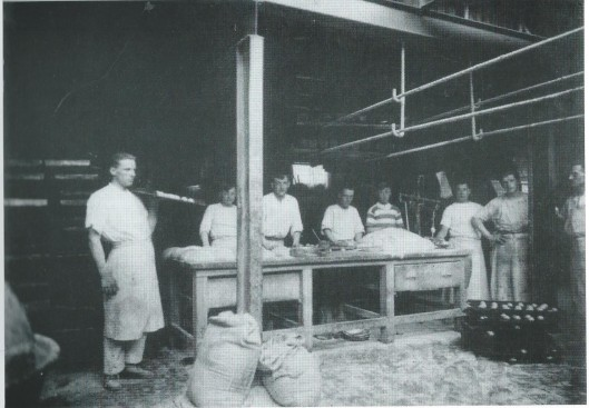 Naast Zwarter was de Coöperatieve Verbruikersvereniging De Samenwerking, afdeling bakkerij, gevestigd. Interieurfoto uit 1928 Tweede van rechts is Jan Westerhoven en derde van links Hein Kroeze. Geheel links zien we Cornelis Koning, die later een sigarenzaak naast de IJzeren Brug had.