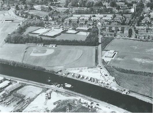 Luchtfoto met op de voorgrond een deel van het industrietterrein Cruquius. Achter de Ringvaart het voormalig woonwagenkamp en verder naar boven zijn het toen nieuwe zwembad en de Sportparklaan te zien