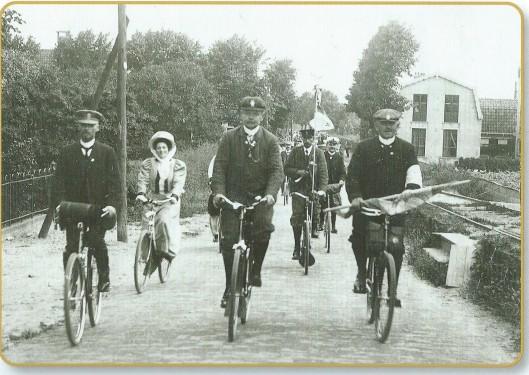 Een feestelijk gezelschap op de fiets komende van Hillegom en rijdende richting Heemstede en Haarlem op de Herenweg in Bennebroek op 18 juli 1908 bij het zilveren jubileum van de ANWB